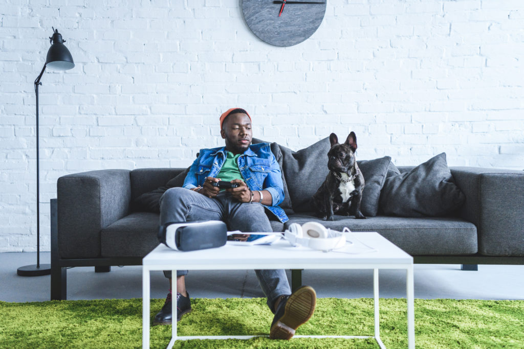 Man with bulldog and VR gear on couch
